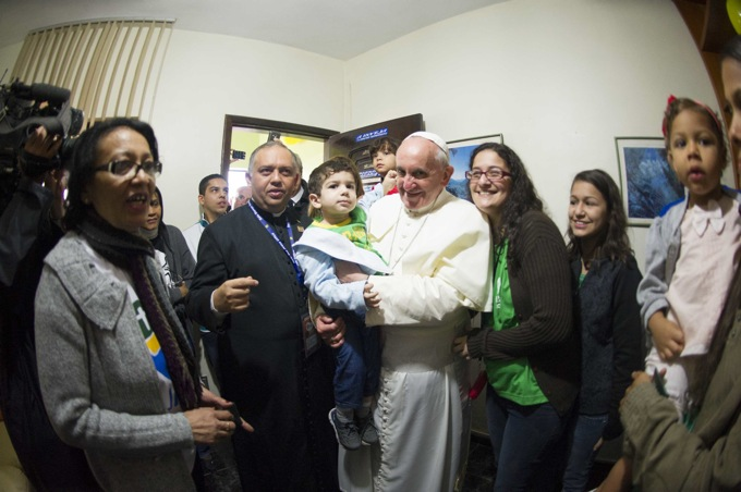 Handout shows Pope Francis holding a boy while on a visit to the Varginha slum in Rio de Janeiro